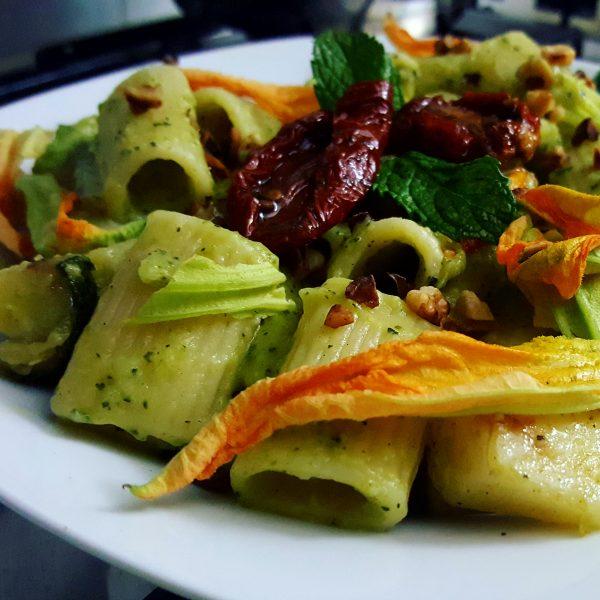 Mezze maniche al pesto di zucchine, con pomodori secchi, nocciole tostate e fiori di zucca