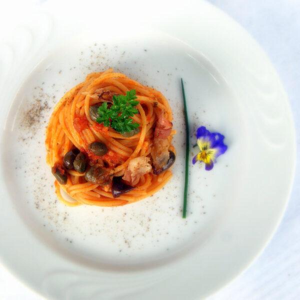 Spaghetti al pomodoro con guanciale croccante, olive taggiasche e capperi